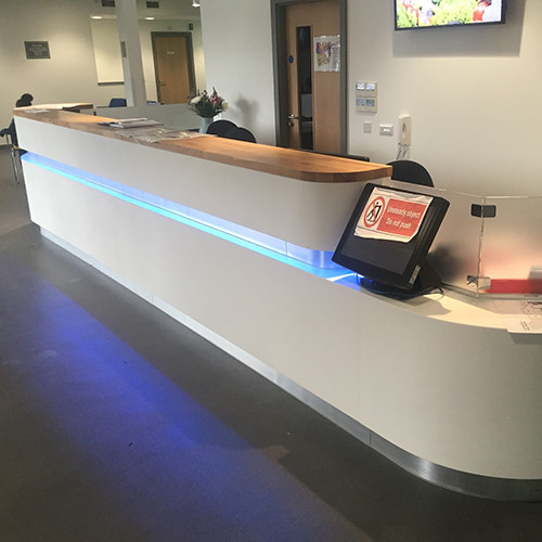 Hanex solid surface reception desk with solid oak top and LED lighting